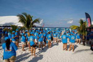 Teilnehmer in blauen T-Shirts am weißen Strand am Fort Myers Beach mit blauem Himmel