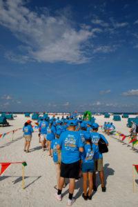 Teilnehmer in Aktions-T-Shirts reihen sich auf am Fort Myers Beach